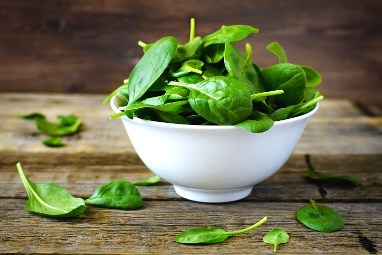 Raw spinach leaves in cup